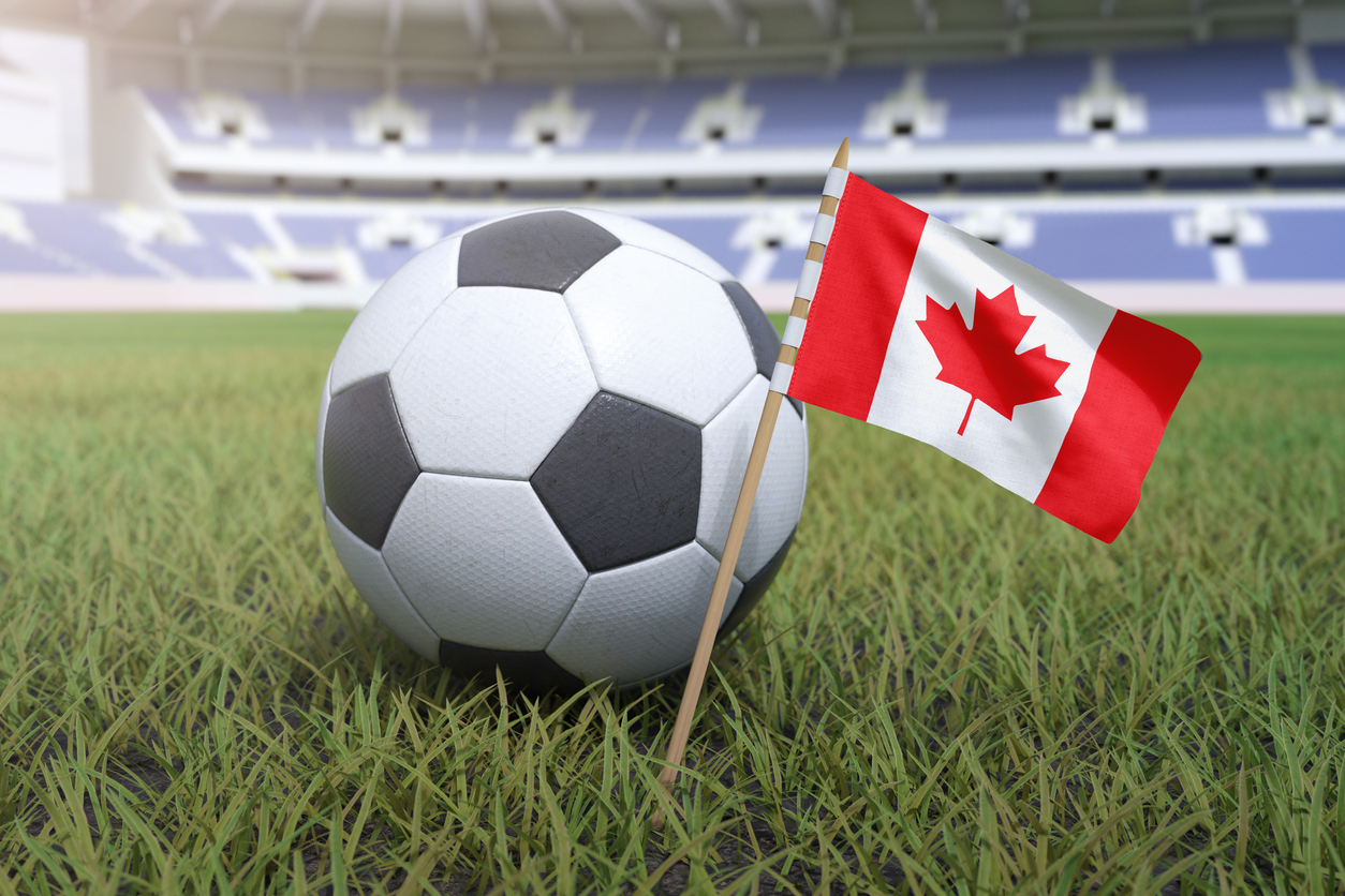 Canada flag in football stadium field with soccer ball on grass